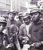 14 iunie 1990: Mineri relaxaţi, zâmbitori la obiectiv pe Bulevardul Magheru, bătând o femeie.